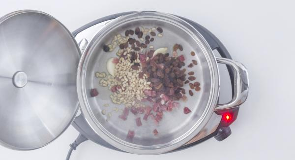 As soon as the Audiotherm beeps on reaching the roasting window, set Navigenio at level 2 and add oil, garlic, ham, pine nuts and raisins. Stir briefly.