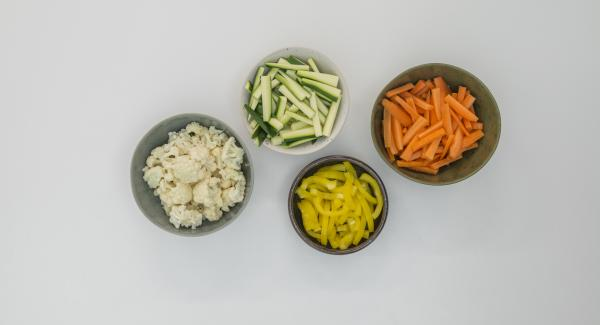 Peel the carrots, clean the zucchini and pepper and cut everything into strips. Clean the cauliflower and cut into small florets.