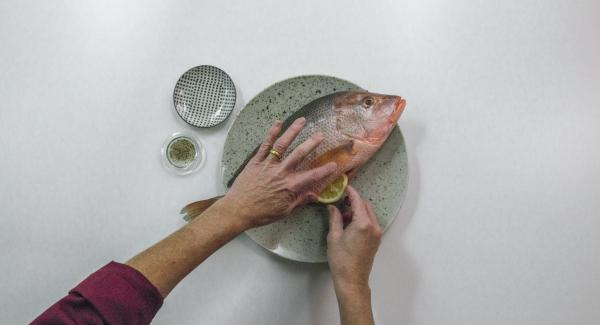 Season the inside and outside of the fish with pepper, fill the belly with the lemon slices.