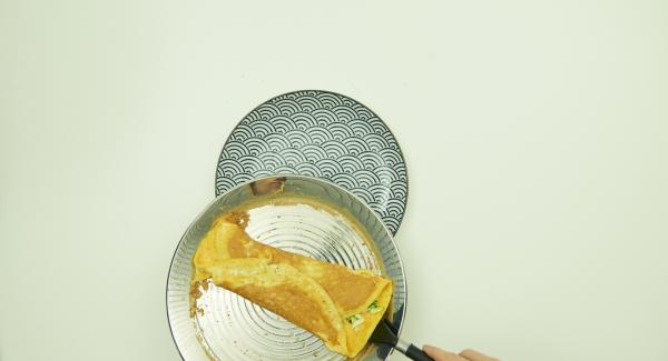 Fold the sides towards the center and glide on plate with spatula.