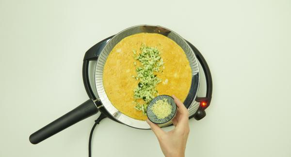 Before the mass in the oPan large has completely thickened, add zucchini and grated cheese in middle of the omelet.