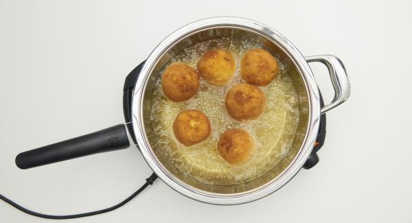 As soon as the Audiotherm beeps on reaching the roasting window, set at level 3, pour the rice balls into the oil and cover with the lid. Deep-fry with the help of the Audiotherm until the turning point at 90 °C is reached. Turn the balls over and deep-fry until they are golden brown, remove them and let them drip off on kitchen paper.