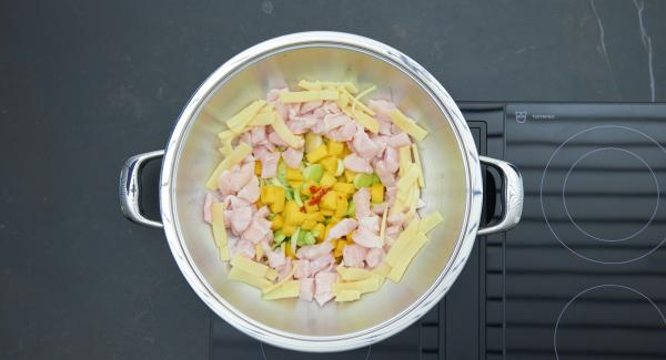 Drip-wet leek and two thirds of the mango cubes into a Wok, spread chili cubes, bamboo shoots and pieces of fish over it.