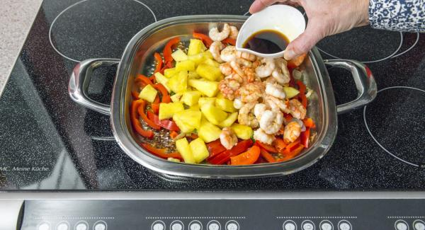 Add prawns and pineapple, reheat everything, season with soy sauce.