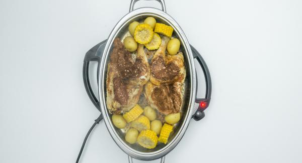 At the end of the cooking time take off lid. Serve the chicken halves together with potatoes and corncob.